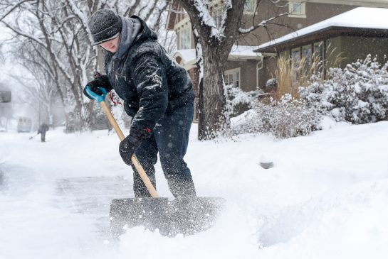 man shoveling snow in kelowna